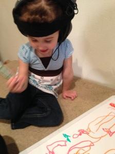 3 year old Alexa wears headphones during writing activity.